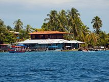 Bocas del Toro coast. Tropical coast with caribbean houses, boats and coconut trees in Carenero island, Bocas del Toro, Panama stock image