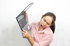 Bocca aperta della giovane donna asiatica arrabbiata che grida alzando il computer portatile fino a per gettarlo via su un fondo  immagini stock
