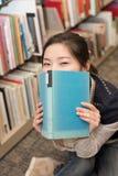 Bocca della copertura dello studente con il libro Immagine Stock