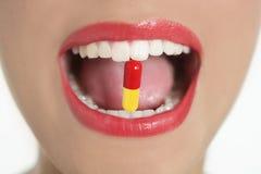 Bocca della donna di bellezza con la pillola della medicina Fotografie Stock