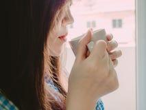 Bocca rossa della ragazza asiatica in pigiami blu e caffè caldo della tenuta per Fotografia Stock
