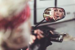 Bocca rouging del pensionato sereno da rossetto fotografie stock