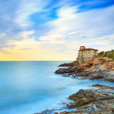 Boccale castle landmark on cliff rock and sea. Tuscany, Italy. L. Boccale castle landmark on cliff rock and sea on sunset. Tuscany, Italy, Europe. Long exposure royalty free stock photography
