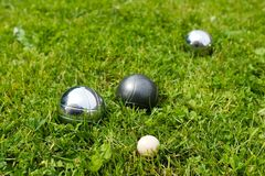 Bocce Balls. Sitting in the green grass, close to the target. -shallow depth of field stock photos