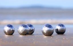 Bocce balls on a sandy beach. A set of steel bocce balls on a sandy beach Royalty Free Stock Photo
