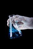 Boccetta chimica della tenuta della mano che mescola liquido blu immagine stock libera da diritti