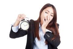 Bocejo asiático novo da mulher de negócios com despertador Fotografia de Stock Royalty Free