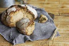 Bochenek żyto chleb na popielatej pielusze na drewnianym stole, wieśniaka styl Fotografia Stock