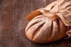 Bochenek żyto chleb w papierowej torbie na drewnianym stole Piekarni tło Fotografia Royalty Free