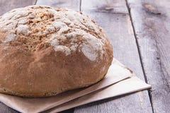 Bochenek chleb na starym drewniany stół, zakończenie Fotografia Stock