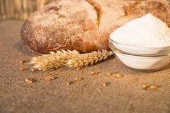 Bochenek chleba lying on the beach na stołu i mąki naczyniu Zdjęcie Stock