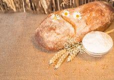 Bochenek chleba lying on the beach na stołu i mąki naczyniu Obraz Stock