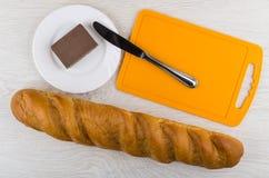 Bochenek chleba, tnącej deski, noża i czekolady masło, Zdjęcia Stock