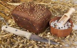Bochenek domowej roboty chleb z czarnej musztardy ziarnami na stole z spikelets żyto owsy, solankowego potrząsacza nóż i sól i obraz royalty free