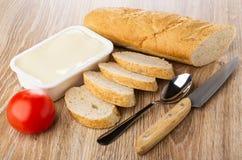 Bochenek i kawałki chleb, plastikowy słój z rozciekłym serem, pomidor, łyżka, nóż na drewnianym stole fotografia royalty free