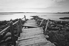 Bochtig oud houten dok op de rotsachtige kust Rusland, Karelië stock foto