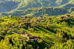 Bochtige weg en een paar huishoudens gebaad door warm zonsonderganglicht, Transsylvanië, Roemenië royalty-vrije stock foto's
