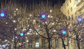 Bochum, Alemania - 12 de diciembre de 2016: Lámparas azules y blancas del LED en los árboles en el fondo del ayuntamiento Bochum fotografía de archivo libre de regalías