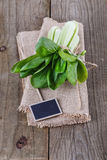 Bock Choy and tag over rustic wooden background Royalty Free Stock Photography