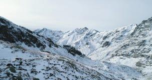 Boczna antena nad zima śnieżnym przełęczem z mountaineering narciarki ludźmi chodzi w górę pięcia góry śnieżne pokrycia zbiory