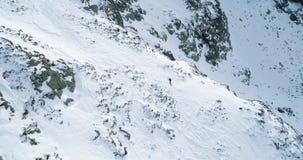 Boczna antena nad zimy śnieżną górą z mountaineering narciarki ludźmi chodzi w górę pięcia śnieg zakrywający góra wierzchołek zbiory