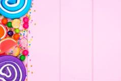 Boczna granica asortowani kolorowi cukierki przeciw różowemu drewnu Fotografia Stock