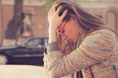 Bocznego profilu zaakcentowana smutna młoda kobieta siedzi outdoors obraz stock
