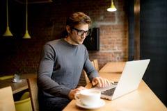 Bocznego widoku biznesmen jest ubranym koszulowego obsiadanie przy stołem w kawiarni i uses laptopie Zdjęcia Stock
