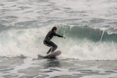Bocznego widoku brunetki facet profesjonalnie jedzie na kipieli na morzu w swimsuit fotografia royalty free