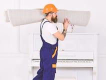 Bocznego widoku faceta odprowadzenie z staczającym się dywanem na jego ramieniu Pracownik niesie białego dywanika poruszający now obrazy royalty free