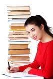 Bocznego widoku kobiety obsiadanie z stertą książki Obrazy Stock
