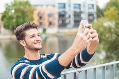 Bocznego widoku młodej radości uśmiechnięty mężczyzna bierze selfie zdjęcia stock