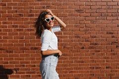 Bocznego widoku portret młoda piękna szczęśliwa kobieta w przypadkowym płótnie przeciw ścianie z cegieł obrazy royalty free