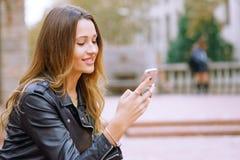 Bocznego widoku portret szczęśliwe kobiety używa mądrze telefon outdoors obraz royalty free