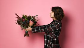 Bocznego widoku profil atrakcyjna m?oda kobieta w ciemnym w kratk? dresst mienia bukiecie kwiaty i dawa? ciebie zdjęcia royalty free