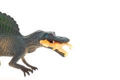 Bocznego widoku spinosaurus popielata zabawka łapie małego disonaur na białym tle Obrazy Stock