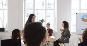 Bocznego widoku uśmiechnięta młoda biznesowa kobieta wchodzić do nowożytnego biuro trzyma pudełko, kolegów rozwesela w górę i kla zbiory