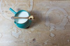 Bocznej rękojeści pucharu ceramiczny miotacz nerkodrzewu mleko z drewnianą łyżką i pojedynczym nerkodrzewem na antykwarskim drewn zdjęcia stock