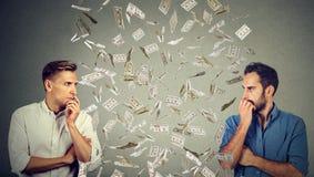 Boczni profilowi biznesmeni patrzeje each inny z pieniądze deszczem in-between fotografia stock
