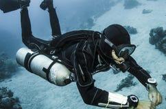 Boczny góra akwalung nurkuje w jasnej błękitne wody Zdjęcia Stock