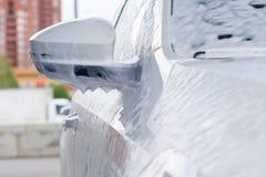 Boczny lustro na białym samochodzie w kontakt pianie na zlew fotografia stock