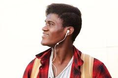 Boczny portret szczęśliwy młody człowiek patrzeje oddalony i uśmiechnięty z słuchawkami Fotografia Royalty Free