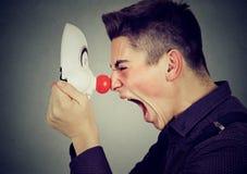 Boczny profilowy gniewny mężczyzna krzyczy przy szczęśliwą błazen maską obrazy royalty free