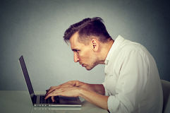 Boczny profilowy młody człowiek pracuje na komputerowym obsiadaniu przy biurkiem Obrazy Royalty Free