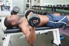 Boczny widok ćwiczy z dumbbells w gym bez koszuli mężczyzna Obrazy Royalty Free