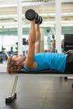 Boczny widok ćwiczy z dumbbells w gym mężczyzna Obraz Royalty Free