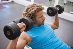Boczny widok ćwiczy z dumbbells w gym mężczyzna Zdjęcie Stock