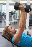 Boczny widok ćwiczy z dumbbells w gym mężczyzna Fotografia Royalty Free