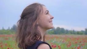 Boczny widok ładna dziewczyna w makowy śródpolny patrzeć daleko od z szczęśliwym szerokim uśmiechem Zwi?zek z natur? Ziele? i zbiory