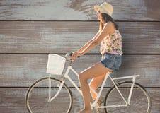 Boczny widok żeński jazda cykl przeciw drewnianej ścianie Obrazy Stock